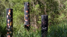 Three black Aboriginal totem poles with orange and red markings including hand prints