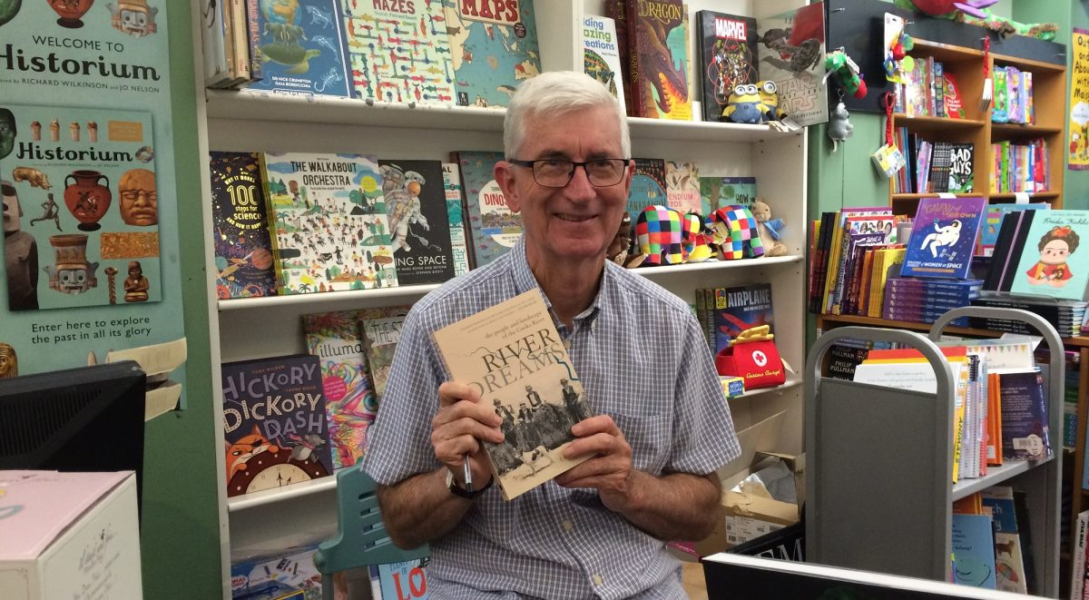 Ian Tyrrell sitting in a bookstore holding his book River Dreams