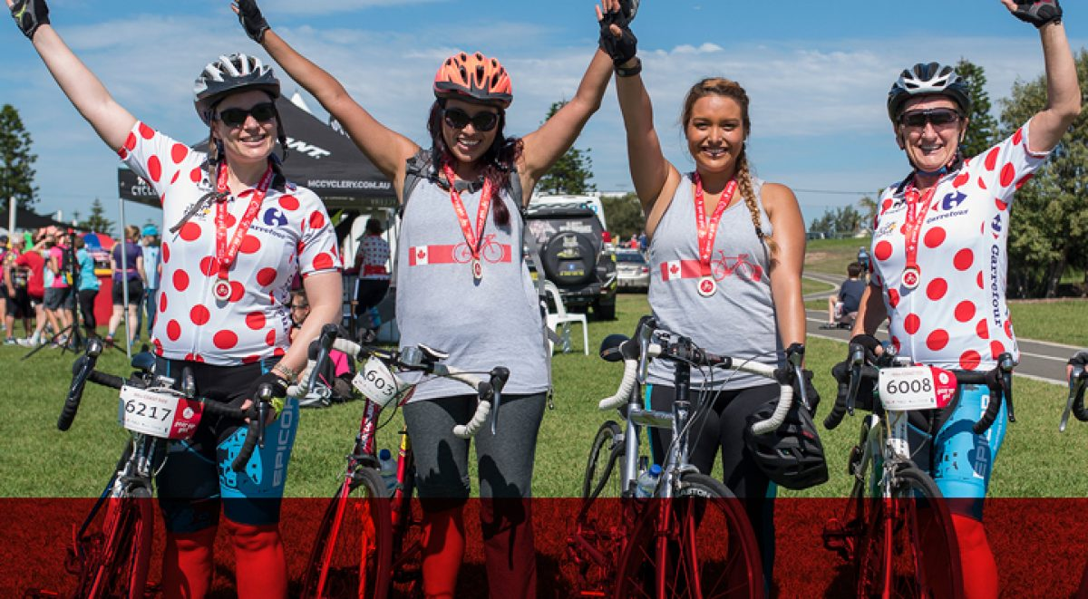 Four women beside their bikes hands raised after completing the trail