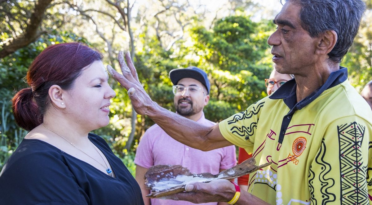 Aboriginal cultural guide painting ochre on the forehead of a