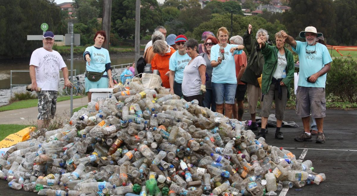 Mudcrabs members stand behind a huge pile of plastic bottles pulled out from the river