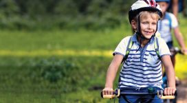 Photo of a young boy cycling beside greenery