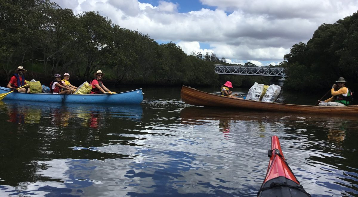 People in kayaks on the river, with rubbish bags inside the kayaks