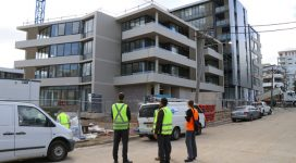 Council rangers wearing flouro yellow vests inspect fencing around an apartment building site