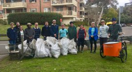 Mudcrabs volunteers stand behind bags filled with rubbish collected from the river