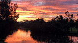 Orange, pink and purple tones in the sky at sunset reflecting in the Cooks RIver
