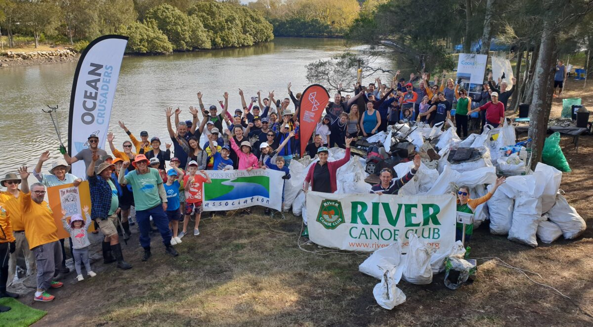 Large group of community members standing beside the river with hands in the air, pictured behind collected bags of rubbish and range of community group banners including River Canoe Club, Mudcrabs and Cooks River Valley Association